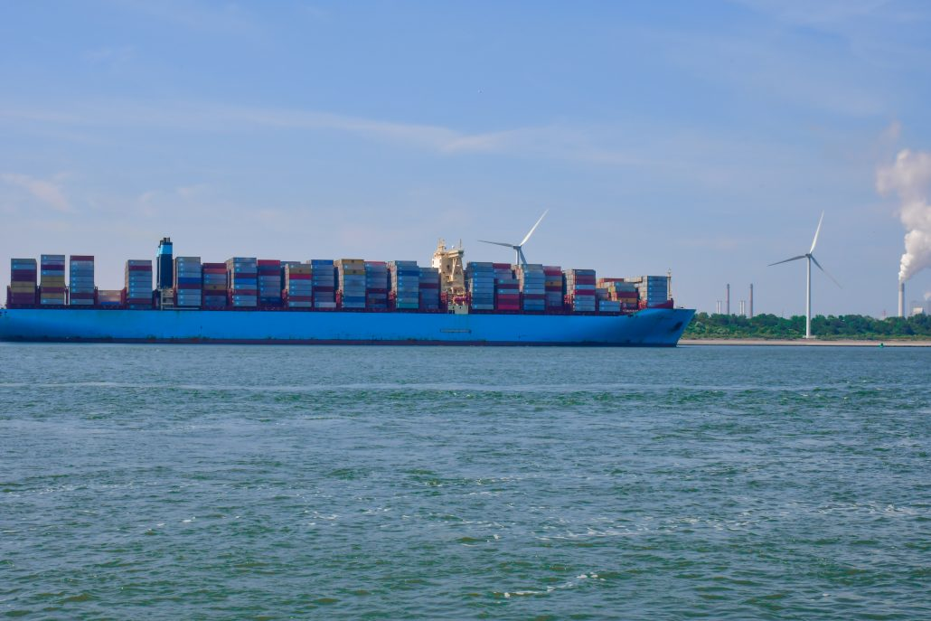 picture of container with behing a shore and wind farms
